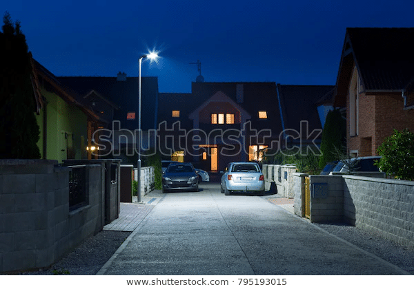 LED street light illuminating road and house at night