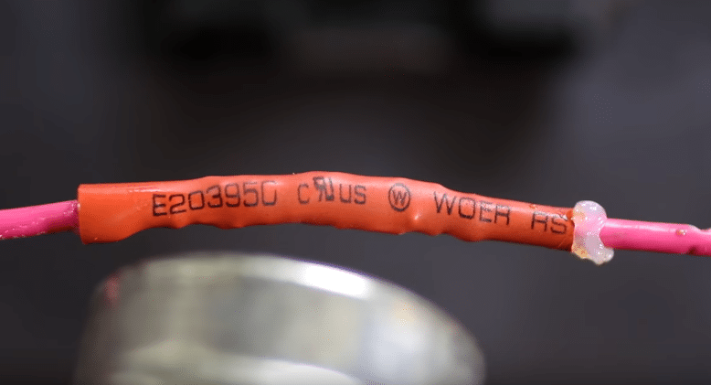 applying heat through heat gun on soldered wire and shrink tube