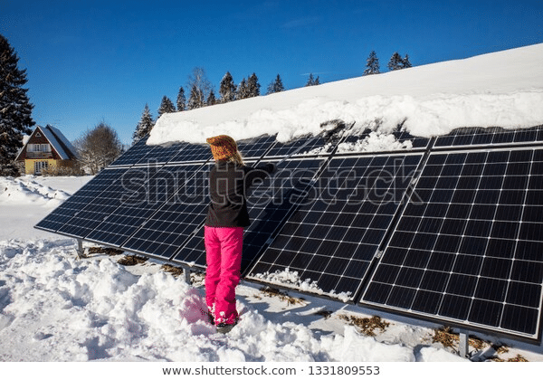 woman cleaning solar panels with snow