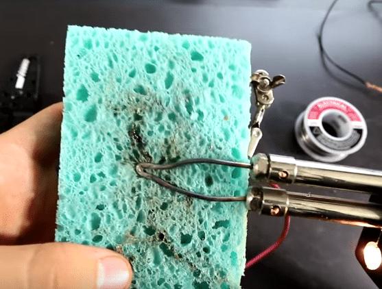 sponge wiping soldering gun before fixing broken wire solder